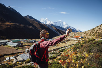 Male hiker taking selfie while standing on mountain against blue sky at Sagarmatha National Park