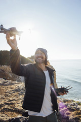 Smiling man flying quadcopter while standing at beach against clear sky during sunny day