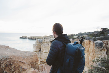 Side view of man with backpack looking at sea while standing on cliff against clear sky