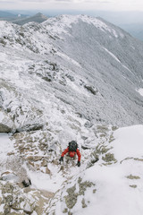 High angle view of backpacker climbing on snowcapped mountain during winter