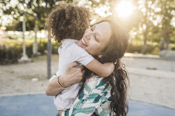 Smiling mother embracing son at park