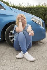 Female in twenties sitting by a broken down car