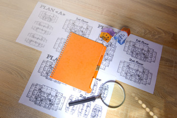 Drawings, paper, notebook and house layouts on the office desk. Construction, architecture, business.