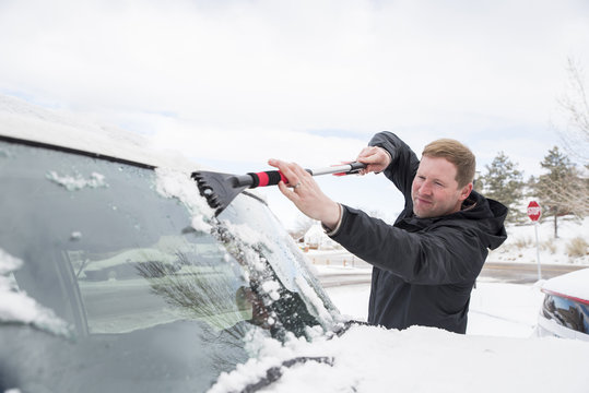 Man cleaning snow from car's windshield during winter