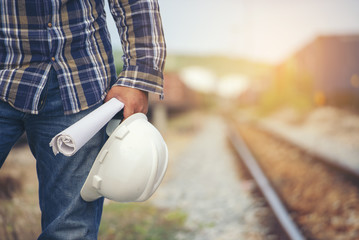 Construction worker Concept.Civil Engineer holding safety hard hat and blue print at Train Station Background,Worker,Foreman or safety officer inspect and work at construction site.