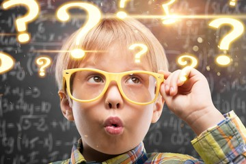 Young boy in glasses on blackboard background