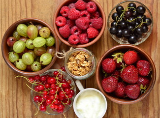Muesli, berries and various ingredients for healthy breakfast, top view