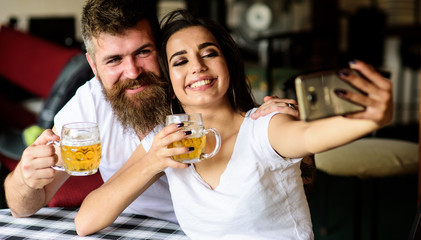 Couple in love on date drinks beer. Couple cheerful mood drinking beer in pub. Man bearded hipster and girl with beer glass full of craft beer. Take selfie photo to remember great date in pub