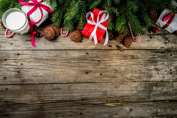 Christmas background with decorations, chocolate cookies and gift boxes on wooden background top view copy space