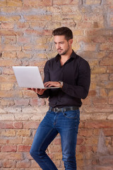 A serious handsome young businessman using a laptop PC in a black shirt.