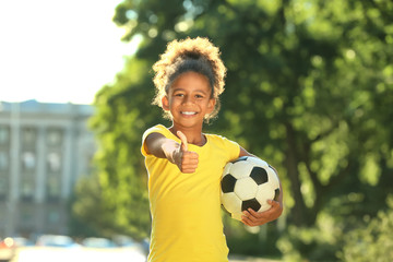 Cute African American girl with soccer ball in park