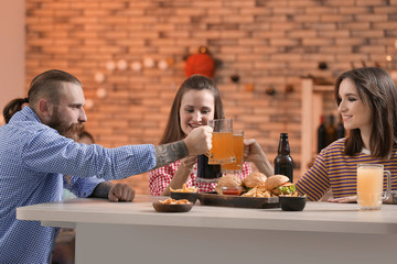 Friends clinking glasses with beer in sport bar