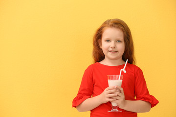 Little girl with glass of delicious milk shake on color background
