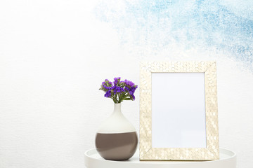 Blank frame and vase with flowers on table near light wall. Mock up for design