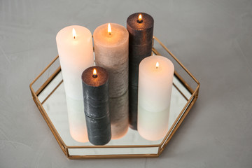 Tray with decorative wax candles on gray table