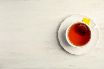 Cup of delicious tea with saucer on wooden background, top view
