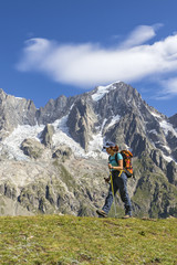 A trekker is walking in front of the Grandes Jorasses during the Mont Blanc hiking tours (Ferret Valley, Courmayeur, Aosta province, Aosta Valley, Italy, Europe).