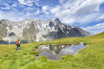 A trekker is walking on the Mont de la Saxe in front of Grandes Jorasses during during the Mont Blanc hiking tours (Ferret Valley, Courmayeur, Aosta province, Aosta Valley, Italy, Europe).