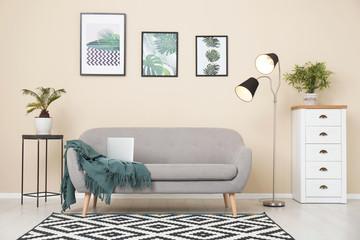 Stylish light room interior with comfortable gray sofa