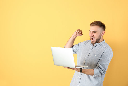 Young handsome man with laptop on color background
