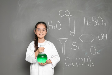 Little school child in laboratory uniform with flask of liquid and chemical formulas on grey background