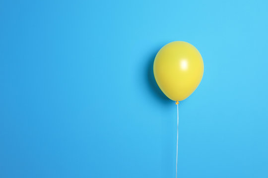 Yellow balloon on color background. Celebration time