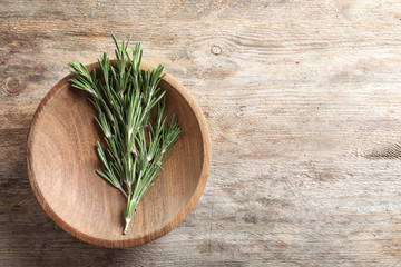 Plate with fresh rosemary twigs on wooden table, top view