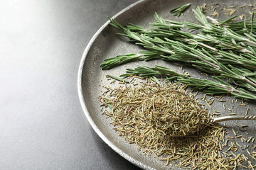 Plate with dried rosemary and twigs on table, closeup