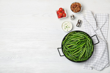 Flat lay composition with tasty green beans on wooden table