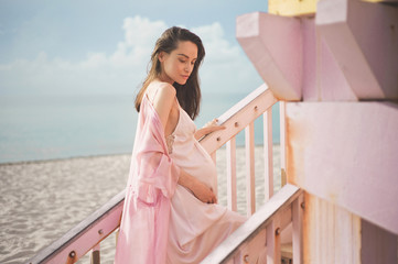Beautiful pregnant woman on the lifeguard tower
