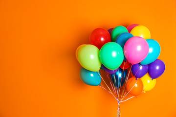 Bunch of bright balloons on color background with space for design Wall mural