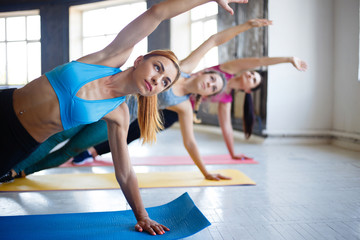 Group workout, women fitness class, active lifestyle, health, teamwork. Sporty women doing side plank to get perfect shape
