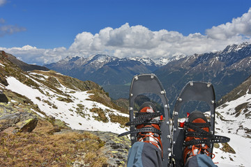 Resting hiker with snowshoes and mountains, blue sky and clouds in the background
