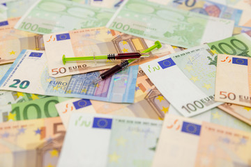 Spread Stack of Euro Banknotes with two syringes on top of them, health costs concept