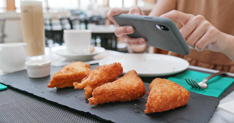 Woman taking photo on fried chicken wind in restaurant