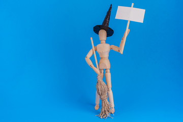 Wooden jointed mannequin doll holding a blank picket sign wearing a witch black hat and holding a witches broom on blue backdrop