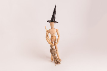 Jointed manikin dummy wearing a black witches hat and holding a broom