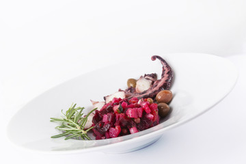 Salad from beet and octopus. Vinegret is a traditional Russian salad made from beets and vegetables. The background is white. Copy space. Horizontal shot.