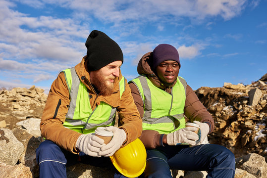 Portrait of two industrial  workers wearing reflective jackets, one of them African, relaxing taking break from work  and chatting on mining worksite outdoors