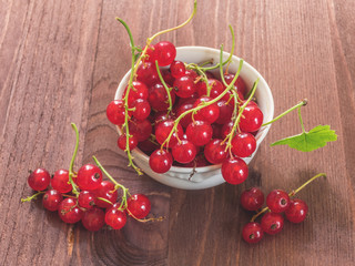 Fresh red currant in white ceramic plate on wood background