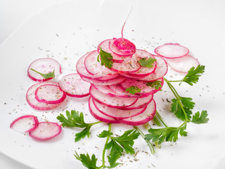 Pink radish is neatly layered on a white plate