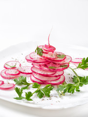 Juicy pink radish cut into a slice with herbs on a white plate