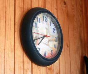 beautiful blue wall clock on wooden board wall closeup