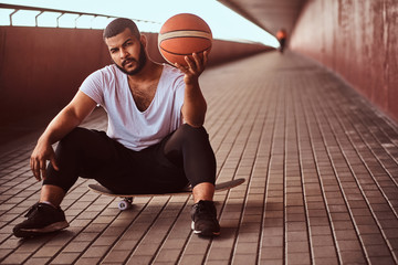 Portrait of a pensive dark-skinned guy dressed in a white shirt and sports shorts holds a basketball while sitting on a skateboard on a footway under bridge.