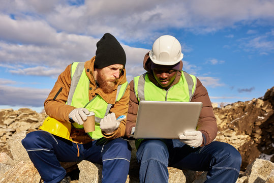 Portrait of two industrial  workers wearing reflective jackets, one of them African, using laptop on mining worksite outdoors