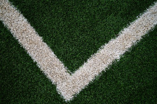 Artificial green grass football / soccer field / pitch & white stripe - close up