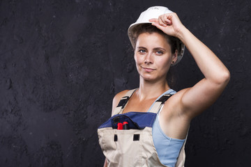 Portrait of beautiful woman worker builder in uniform with white helmet. cute young builder girl in work clothes