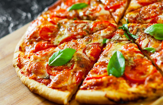 sliced Pizza with Mozzarella cheese, Tomatoes, pepper, Spices and Fresh Basil. Italian pizza. Pizza Margherita or Margarita