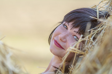 Portrait cute happy beautiful female brunette with red lipstick against a background of wheat field at the time of the sunset