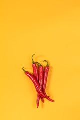 Red hot chili pepper on yellow surface. Beautiful minimalist food art background